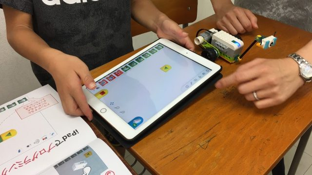 先生に教わりながらロボットプログラミングをする男の子